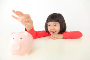 貯金箱にお金を入れるおかっぱの女の子の写真素材 [FYI02030211]