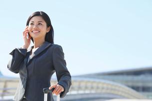 スーツケースを持ち携帯で話をするビジネスウーマンの写真素材 [FYI02030233]