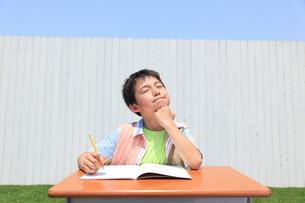 青空の下で勉強する男の子の写真素材 [FYI02030234]