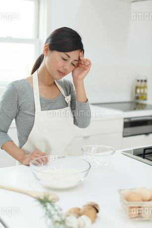 料理中に頭が痛くなった女性の写真素材 [FYI02030263]