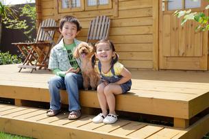 ログハウスの前に座る男の子と女の子と犬の写真素材 [FYI02030299]