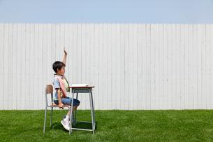 青空の下で勉強する男の子の写真素材 [FYI02030306]