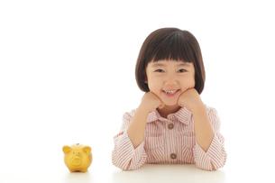 貯金箱と頬杖をついて考える女の子の写真素材 [FYI02030332]