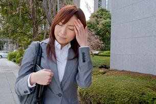 頭を押さえる女性の写真素材 [FYI02030346]