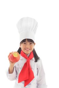 りんごを持つシェフの女の子の写真素材 [FYI02030349]