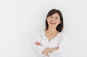 白い壁の前で腕を組み笑う女性の写真素材 [FYI02030352]