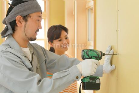 大工さんに作業を習う女性の写真素材 [FYI02030360]