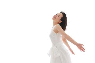 白いワンピースを着てポーズをとる若い女性の写真素材 [FYI02030370]
