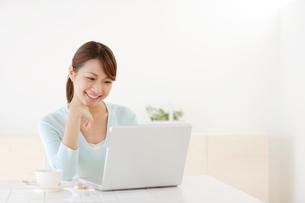お茶を飲みながらパソコンをする若い女性の写真素材 [FYI02030382]
