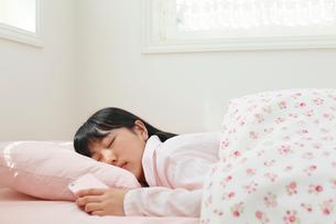 スマホを手に寝坊をする女の子の写真素材 [FYI02030386]