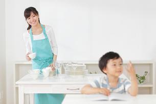 食器を片づけるお母さんと勉強をする男の子の写真素材 [FYI02030405]