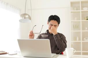 デスクワークで目が疲れた男性の写真素材 [FYI02030411]
