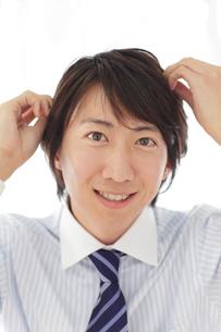出勤前に髪の毛を整えるビジネスマンの写真素材 [FYI02030415]