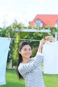 広い庭で洗濯物を干す女性の写真素材 [FYI02030435]