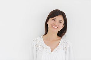 白い壁の前で微笑みながら考える女性の写真素材 [FYI02030436]