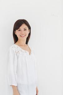 白い壁の前で微笑む女性の写真素材 [FYI02030442]