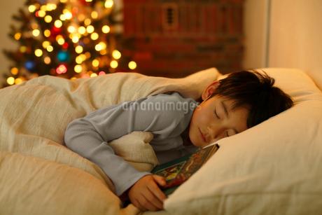 クリスマスツリーのある寝室で眠る男の子の写真素材 [FYI02030443]