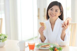 朝食を食べながらスマートフォンを持つバスローブ姿の女性の写真素材 [FYI02030455]