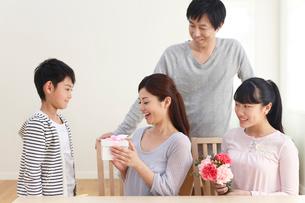 母の日のプレゼントを贈る子どもたちと見守るお父さんの写真素材 [FYI02030458]