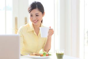 パソコンを見ながら朝食を食べる女性の写真素材 [FYI02030462]