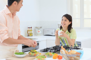 料理をする夫と見守る妻の写真素材 [FYI02030468]