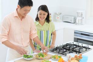料理をする夫と見守る妻の写真素材 [FYI02030469]