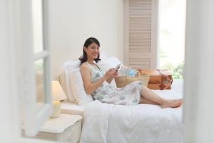 旅行先の南国のホテルでタブレットを見る女性の写真素材 [FYI02030476]