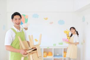 教室の片づけをする男女の幼稚園の先生の写真素材 [FYI02030484]