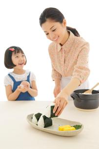 おにぎりを作るおかっぱの女の子とお母さんの写真素材 [FYI02030492]