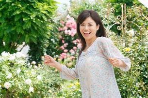 満開のローズガーデンで休日を楽しむ女性の写真素材 [FYI02030495]