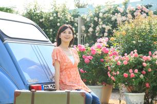 水色の可愛い車とスーツケースと若い女性の写真素材 [FYI02030533]