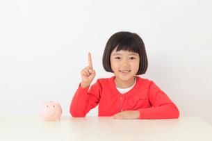 貯金箱と指差しポーズのおかっぱの女の子の写真素材 [FYI02030551]