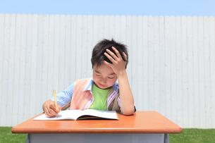 青空の下で勉強する男の子の写真素材 [FYI02030570]