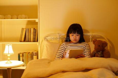 ベッドでタブレットを操作する女の子の写真素材 [FYI02030590]