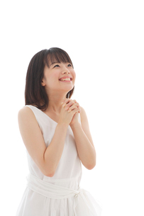 白いワンピースを着て願い事をする若い女性の写真素材 [FYI02030597]