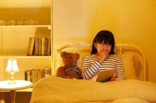 ベッドでタブレットを操作する女の子の写真素材 [FYI02030633]