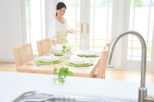 ダイニングキッチンでテーブルセッティングをする女性の写真素材 [FYI02030635]