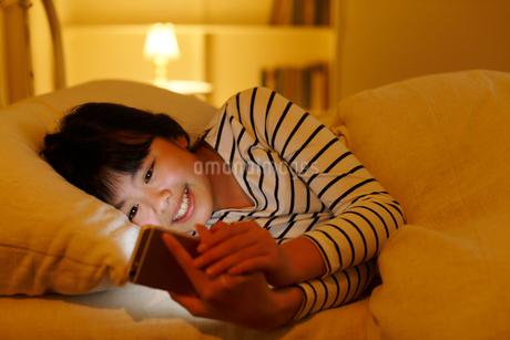 真夜中にベッドでスマホを操作する女の子の写真素材 [FYI02030637]
