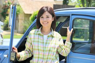 水色の可愛い車から降りる若い女性の写真素材 [FYI02030642]