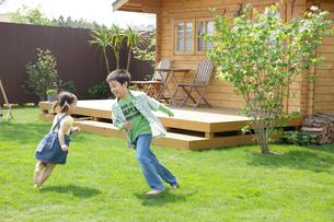 ログハウスの庭で遊ぶ男の子と女の子の写真素材 [FYI02030645]