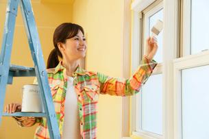 窓枠にペンキを塗る女性の写真素材 [FYI02030648]