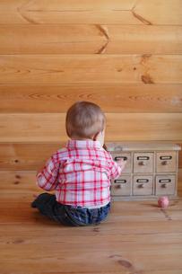 木の床に座って遊ぶ赤ちゃんの後ろ姿の写真素材 [FYI02030665]