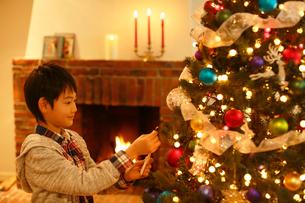 クリスマスツリーに飾り付けをする男の子の写真素材 [FYI02030666]