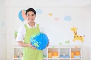 教室の片づけをする男の幼稚園の先生の写真素材 [FYI02030667]