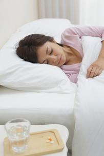 体調不良で寝る女性とテーブルに置かれた薬の写真素材 [FYI02030697]