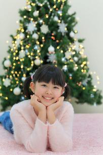 クリスマスツリーのある部屋でくつろぐ女の子の写真素材 [FYI02030698]
