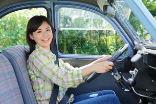 水色の可愛い車を運転する若い女性の写真素材 [FYI02030703]