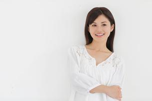 白い壁の前で微笑みながら考える女性の写真素材 [FYI02030720]