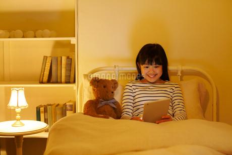 ベッドでタブレットを操作する女の子の写真素材 [FYI02030744]