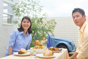 庭でランチを楽しむ夫婦の写真素材 [FYI02030771]